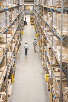 Two men walking in factory warehouse - DIGF01777