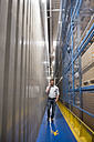 Man in passageway in a factory talking on cell phone - DIGF01780