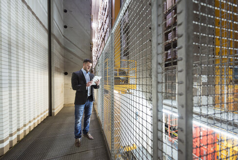 Man in automatized high rack warehouse looking at tablet - DIGF01783