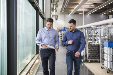 Two men walking in factory shop floor talking about product - DIGF01831