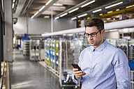 Businessman in factory shop floor looking at cell phone - DIGF01837