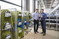 Two men in factory shop floor examining product - DIGF01843