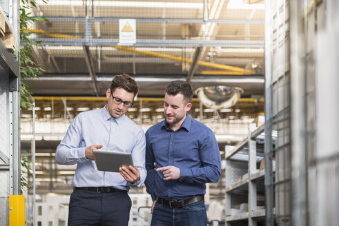 Two men with tablet talking in factory shop floor - DIGF01852