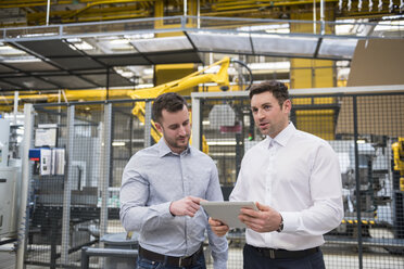 Two men with tablet talking in factory shop floor - DIGF01858