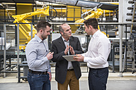 Three men with tablet talking in factory shop floor - DIGF01861