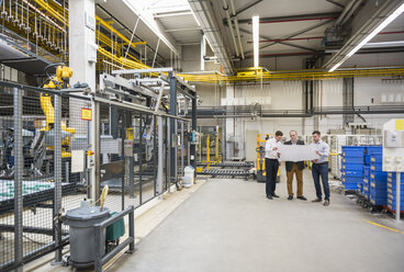 Three men with blueprint talking in factory shop floor - DIGF01867