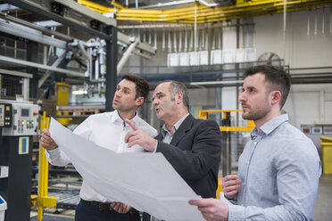 Three men with blueprint talking in factory shop floor - DIGF01870