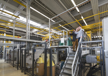 Two men talking in factory shop floor - DIGF01873