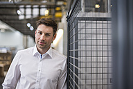 Portrait of confident businessman in factory shop floor - DIGF01876