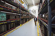 Businessman walking in factory storehouse looking at cell phone - DIGF01879