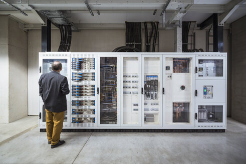 Businessman in factory looking at buffer storage of a photovoltaic plant - DIGF01882