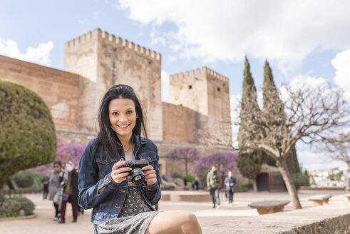 Spain, Granada, smiling young woman with camera at the Alhambra - JASF01728