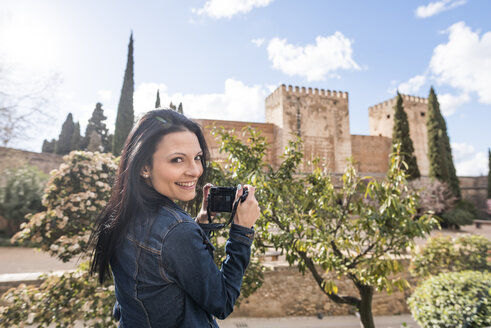 Spain, Granada, smiling young woman taking pictures at the Alhambra - JASF01731