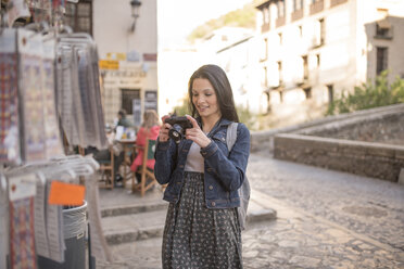 Spain, Granada, smiling young woman with camera at Albayzin district - JASF01749