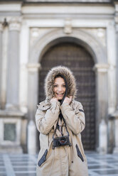 Spain, Granada, portrait of happy young woman with camera outdoors - JASF01752