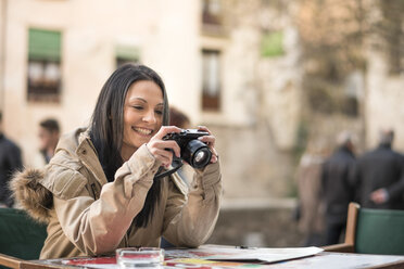 Spain, Granada, smiling young woman with camera at Albayzin district - JASF01755