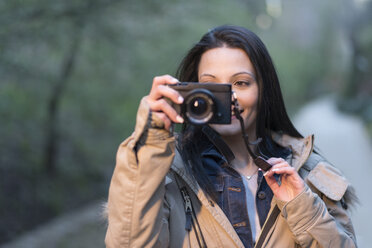 Smiling young woman holding camera outdoors - JASF01761