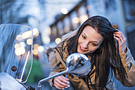 Young woman checking her look in wing mnirror of a motor scooter - JASF01764