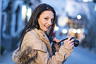 Spain, Granada, young woman with camera at Albayzin district at dusk - JASF01767
