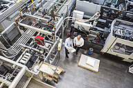 Top view of two men in factory shop floor talking about product - DIGF01893