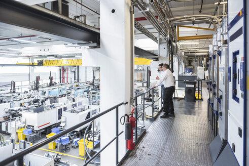 Two men talking in factory shop floor - DIGF01911