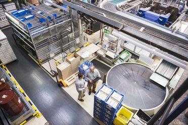 Top view of two men talking in factory shop floor - DIGF01959