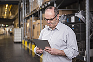 Man using tablet in factory warehouse - DIGF01971