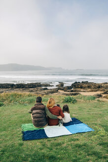 Back view of family with dog sitting on blanket at the coast - DAPF00697