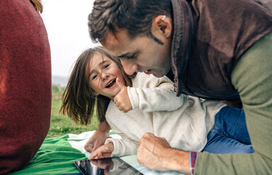 Happy girl and her father using tablet lying on blanket outdoors - DAPF00703