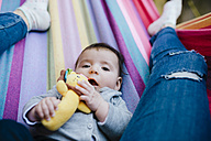 Portrait of baby girl lying on a hammock with her mother - GEMF01593