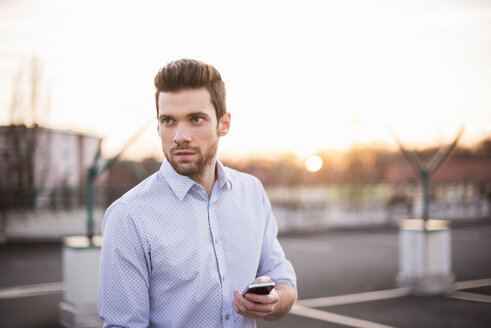 Portrait of young man with cell phone looking at distance - DIGF02016