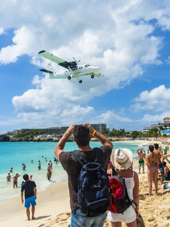 Caribbean, Sint Maarten, Philippsburg, Simson Bay Village, tourists on beach watching and taking pictures of plane approaching airport - AM05378