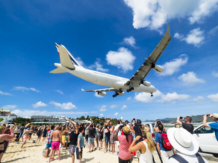 Caribbean, Sint Maarten, Philippsburg, Simson Bay Village, tourists on beach watching and taking pictures of plane approaching airport - AM05381