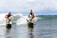 Two girls surfing in ocean - KNTF00825