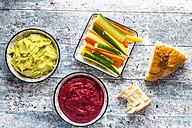 Bowls of beetroot hummus and avocado hummus, crudites and flat bread - SARF03309