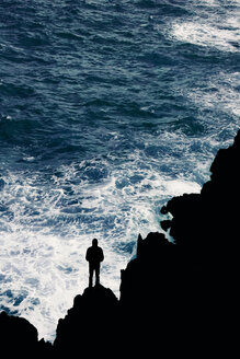 Portugal, Madeira, silhouette of man at rocky coast by the sea - DWIF00849