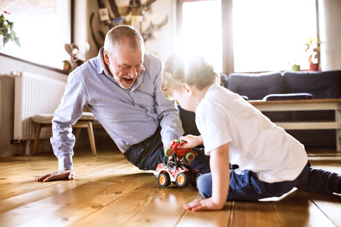 Grandfather and grandson playing at home with toys - HAPF01499