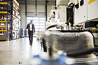 Businessman walking in factory shop floor looking on the phone - DIGF02018