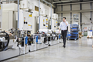 Man walking in factory shop floor talking on the phone - DIGF02021