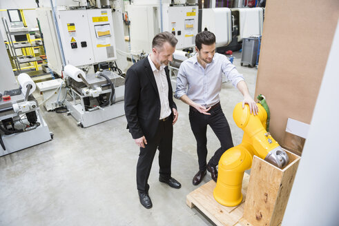 Two men talking in factory shop floor at industrial robot - DIGF02024