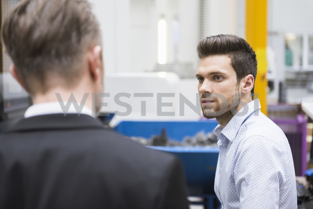 Young man looking at manager in factory - DIGF02030