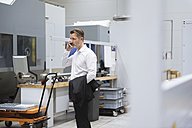 Businessman in factory shop floor on the phone - DIGF02033