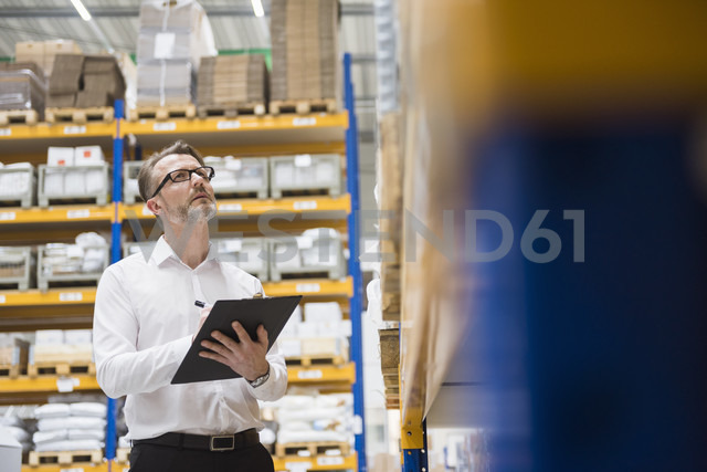 Man in storehouse taking notes - DIGF02039