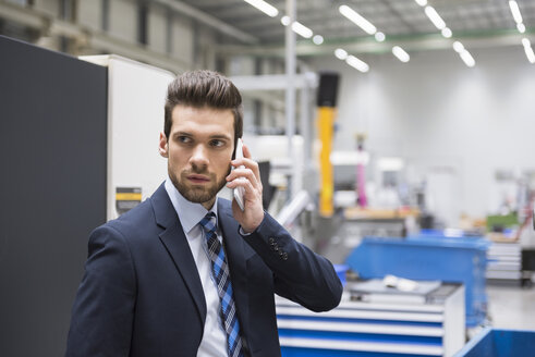 Businessman in factory shop floor on the phone - DIGF02042