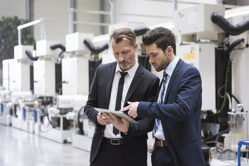 Two businessmen sharing tablet in factory shop floor - DIGF02048