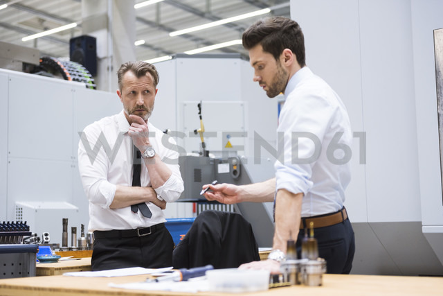 Two businessmen at table in factory shop floor discussing - DIGF02057