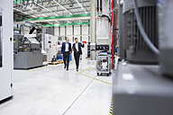 Two men walking and talking in factory shop floor - DIGF02069
