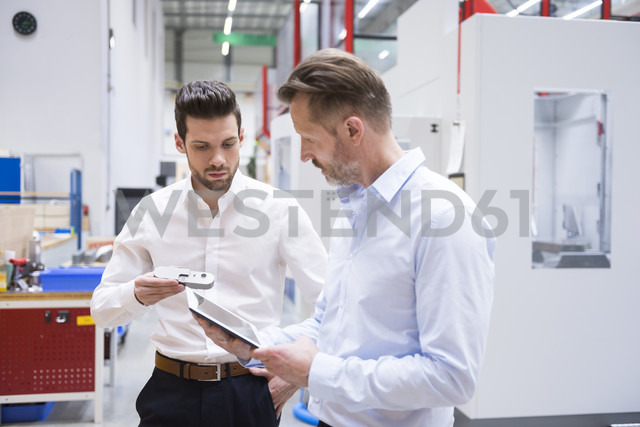 Two men with tablet and product in factory shop floor - DIGF02078