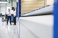 Two businessmen standing in factory shop floor - DIGF02084