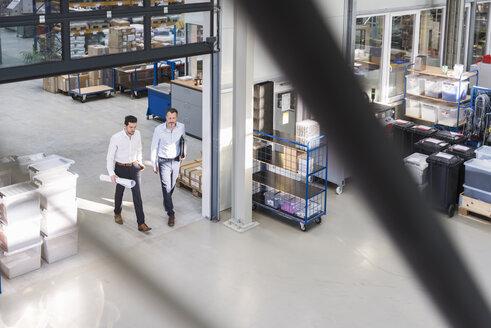 Two businessmen walking in factory shop floor - DIGF02087
